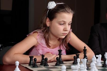 Teenage girl 12-13 years old playing chess  photo