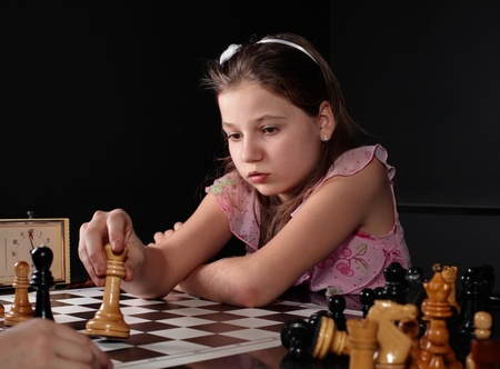 early teens: Teenage girl 12-13 years old playing chess. Check Stock Photo