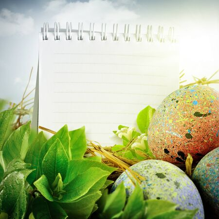 Easter eggs design. With painted eggs, green leaf, notepad, & flower photo