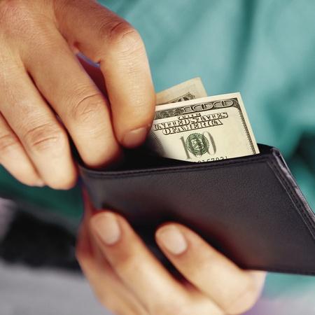 poner algo de dinero de dólares de una cartera Foto de archivo