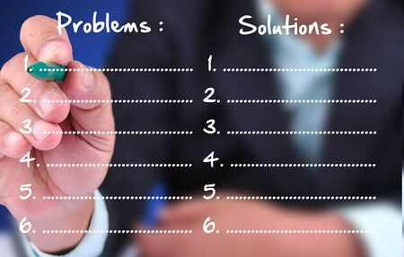 collate: business man writing problem and solution. With list Stock Photo