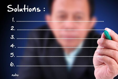 relate: business man writing solution list with note Stock Photo