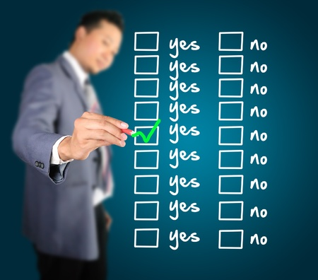Business man writing yes or no in checkbox list photo