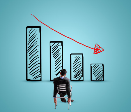 decline: Businessman looking for decreasing graph