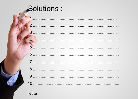 collate: businessman writing solution list with note