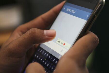 attractive hands writing love conversation on a smart phone Фото со стока - 129786678