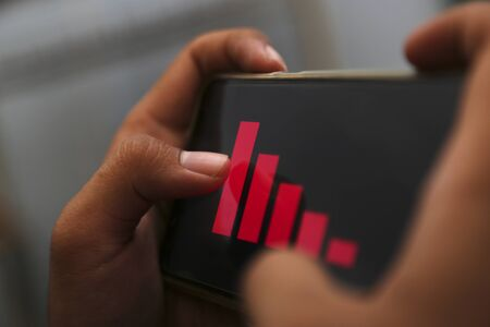 attractive hands showing decrease graph on a smart phone 版權商用圖片
