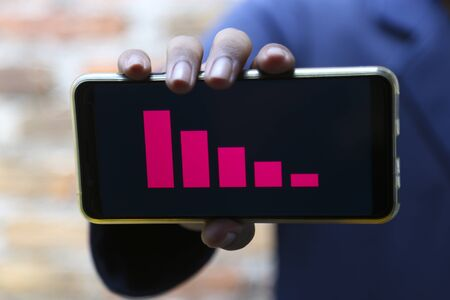 attractive hands showing decrease graph on a smart phone