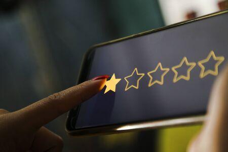 hands showing one stars on a smart phone 版權商用圖片