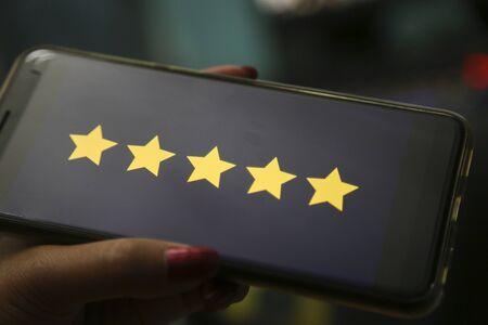 hands showing five stars on a smart phone 版權商用圖片