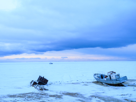 Frozen Lake Baikal, fishing boat in the ice Stock Photo