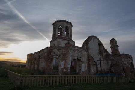 A very old ruined Church of the fifteenth century in the light of the sunset Stock Photo