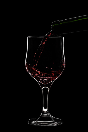 A glass of red wine is pouring wine from a bottle of red . Filmed in close-up glass, where you pour the wine from the bottle.