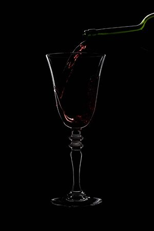Glass of a red wine with threaded on the stem is pouring wine from a bottle of red . Filmed in close-up glass, where you pour the wine from the bottle.