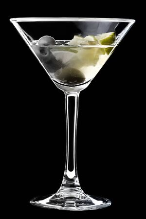Dirty martini in a glass served with olives and a sliceses of lime. A glass with cocktail isolated on a black background.