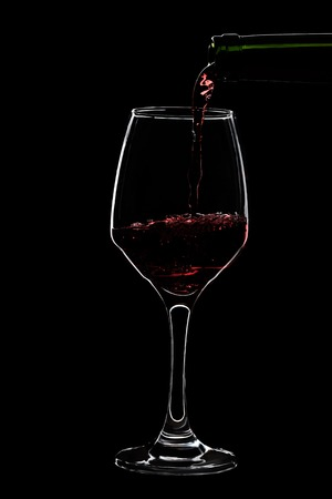 Glass of red wine is pouring wine from a bottle of red . Filmed in close-up glass, where you pour the wine from the bottle. Stock Photo