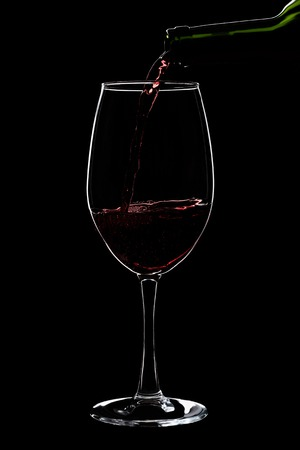 A large glass of red wine is pouring wine from a bottle of red . Filmed in close-up glass, where you pour the wine from the bottle.