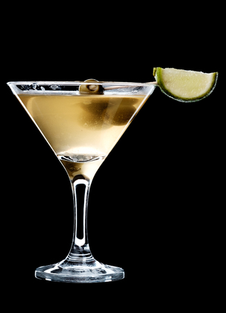 A dirty martini in a glass served with olives and a slice of lime. A glass with cocktail isolated on a black background.