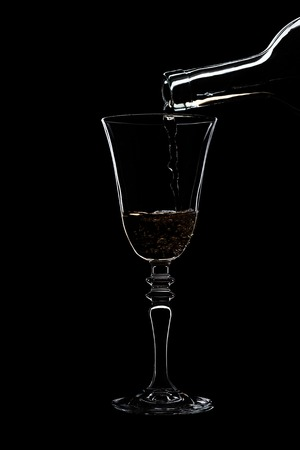 Glass of white wine with threaded on the stem is pouring wine from a bottle of white. Filmed in close-up glass, where you pour the wine from the bottle. Stock Photo