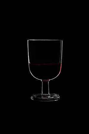 A low glass with red wine isolated on black background.