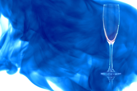 An empty champagne flute on white background enveloped in puff of blue smoke.