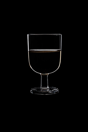 A low glass with white wine isolated on black background. Stock Photo