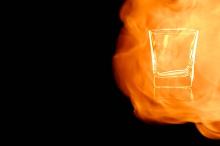 En empty shot of vodka or tequila isolated on black background in the fire flames.