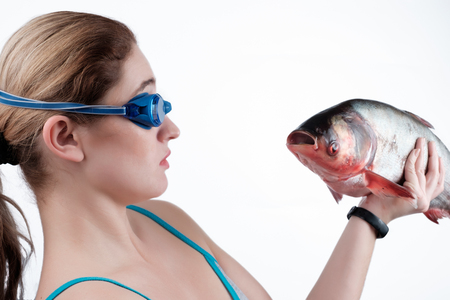 The girl looks at the fish, holding it in her left hand isolated over white background.