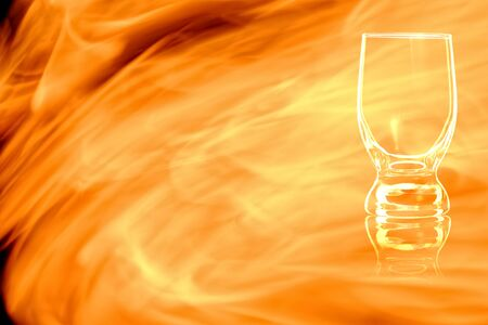 An empty glass of water isolated on black background in the fire flames.
