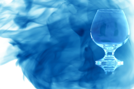 Empty glass of cognac on the leg on white background enveloped in puff of blue smoke.