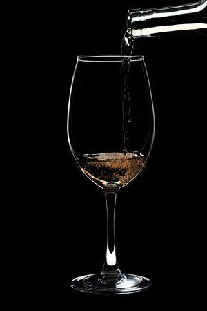 A large glass of white wine is pouring wine from a bottle of white. Filmed in close-up glass, where you pour the wine from the bottle.
