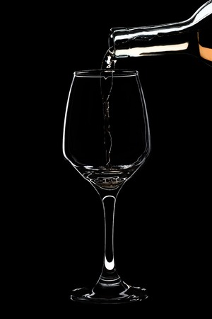 Glass of white wine is pouring wine from a bottle of white. Filmed in close-up glass, where you pour the wine from the bottle. Banque d'images