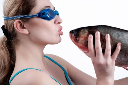 A girl holding a big fish isolated over white background. The girl and the fish look at each other. The girl pulls the lips to the fish.