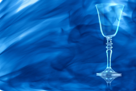 Empty red wine glass on the stem with thread on white background enveloped in puff of blue smoke.
