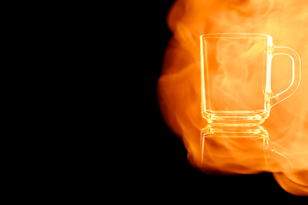 En empty glass mug for tea isolated on black background in the fire flames.
