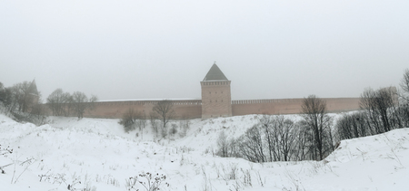 Fortress wall of Smolensk in the winter fog. Part of the fortress wall and tower in winter. Along the wall around the snow. Banque d'images