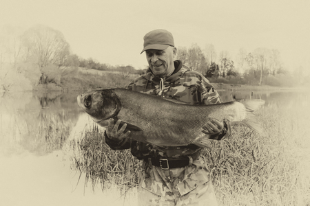 Lucky fisherman holds a large fish that he caught. Vintage photo.