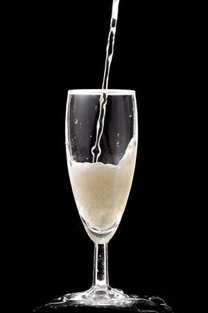 Champagne glass on a black background. The glass in which champagne is poured, which plays with gold paint and bubbles. Banque d'images