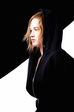 Young beautiful girl on a black and white photo. Side view - girl shot in the hoodie, staring into the distance myself. Dressed in a black jacket with a lock. On the hood.