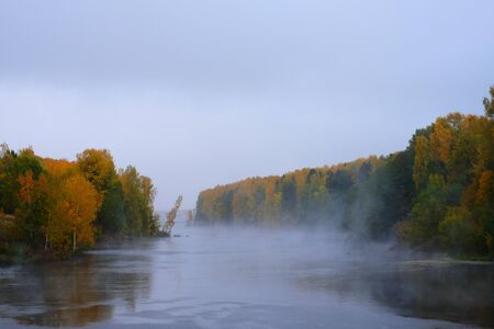 A white mist rises above the river in the autumn forest. Beautiful views of the autumn landscape in the forest, through which flows the river, over the river rises a fog.