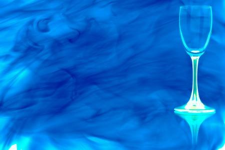 Empty liquor glass on the blue leg on white background enveloped in puff of blue smoke.