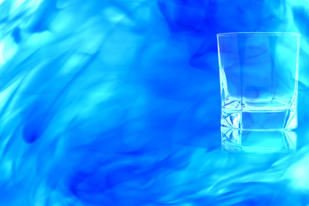 An empty glass of whiskey on white background enveloped in puff of blue smoke.