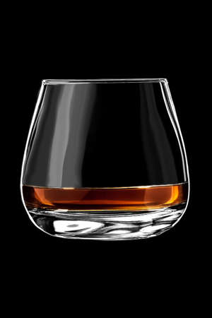 A glass of cognac or brandy isolated on a black background.