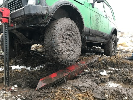 A drty car lift rack Jack. The green machine is raised out of the mud by means of a rack Jack. Around the mud and snow. Banque d'images