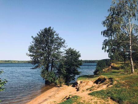 Summer day on the river. Calm expanse of water, sandy shore, green trees. On the other side dense forest.