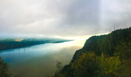 Fog rises over the river. The mist rises high above the river. Around the forest, the view from the top of the mountain.