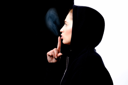 Beautiful girl on black and white background. Girl shot in profile, on his head wearing a hood, index finger she is holding near her mouth, to the top of the finger, the smoke.