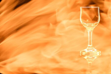 En empty glass of liqueur or cocktail sour isolated on black background in the fire flames.