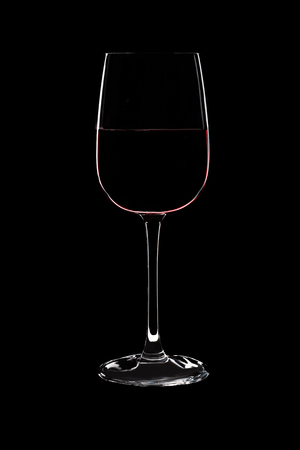 Large glass with red wine isolated on black background.