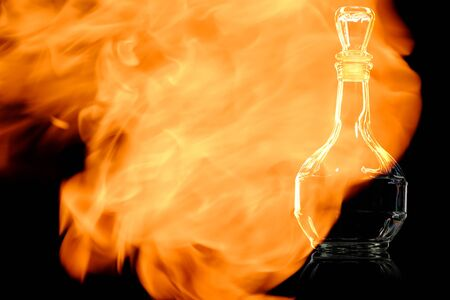Empty decanter in the fire flames isolated on black background in the fire flames. Banque d'images